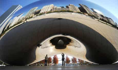 People admire Cloud Gate by British artist Anish Kapoor at the AT&T Plaza in Millennium Park that reflects the downtown skyline in Chicago, Illinois