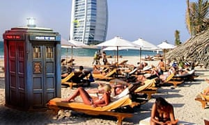 Doctor Who's Tardis on a beach in Dubai with the Burj Al Arab hotel in the background