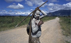 Dani tribeswoman walking on a road through the Baliem Valley, Indonesia, 1989