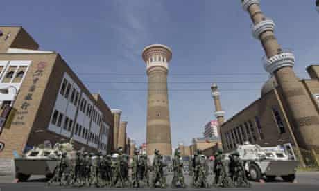 Security forces on patrol near a mosque in Urumqi.