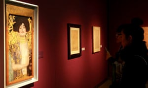 A visitor stands in front of a painting by Klimt