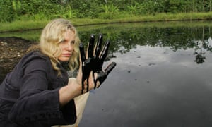 Actress Daryl Hannah scoops oil from a pool in Ecuador, where locals are suing Chevron Texaco