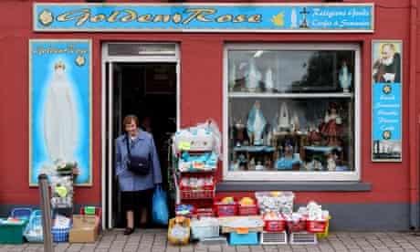 Living on a prayer … a woman exits a Roman Catholic memorabilia shop in Knock, County Mayo, Ireland.