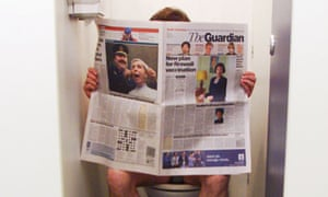 A man sitting on the toilet reading a newspaper