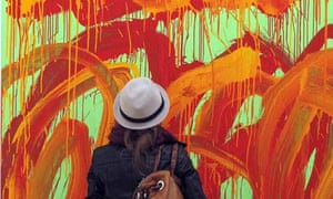 A woman takes in a painting by Cy Twombly