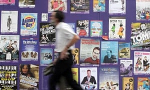 A man walks in front of Edinburgh festival posters