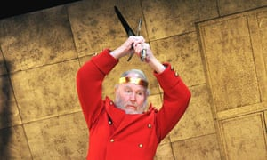 Tim Pigott-Smith as King Lear in a redcoat holding a sword over his head about to strike