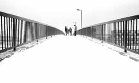 Joy Division, by Kevin Cummins, standing in the distance on the snowy Princess Parkway bridge