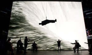 Survivor: string musicians against a huge video screen with a man suspended horizontally overhead