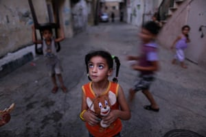 A Palestinian girl holds her toy while playing with other children in an alley