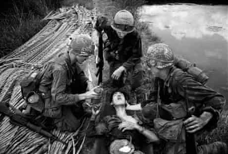 American G.I's showing compassion toward an injured Vietcong soldier