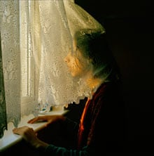 A young girl from East London looking out of a window