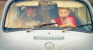 Two boys playing in a Beetle car