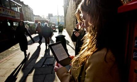 Woman reads ebook, Kindle in street