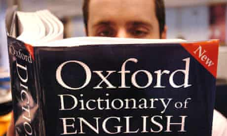 A man reads a copy of the Oxford English Dictionary