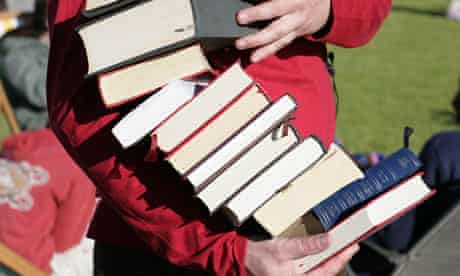Man holding a pile of books