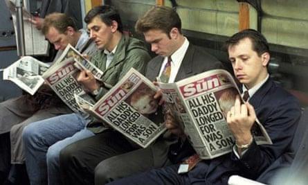 Men reading the Sun on the tube train