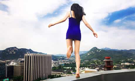 Self-portrait of South Korean artist Ahn Jun, running along a tall building in Seoul
