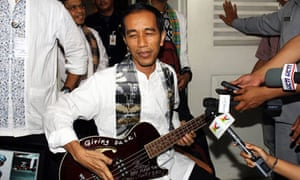 Jakarta governor Joko Widodo holding a bass guitar gifted to him by Robert Trujillo of Metallica