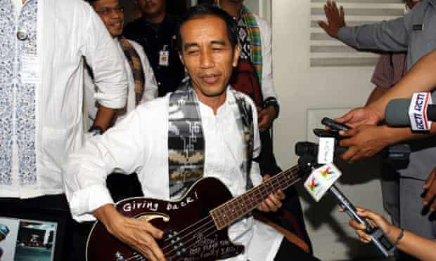 Jakarta governor Joko Widodo holding a bass guitar gifted to him by Robert Trujillo of Metallica