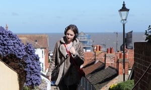 Woman on streets of Aldeburgh with headphones, part of Punchdrunk's The Borough.