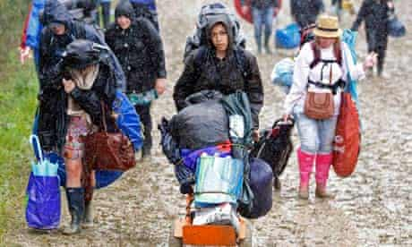 Glastonbury 2011 festival goers push their belongings through the mud