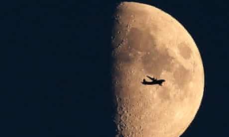 Plane flies in front of the moon