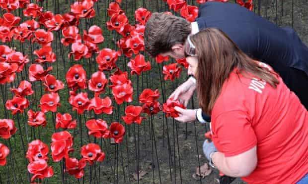 The US ambassador examines a poppy.