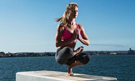 Woman practicing yoga on concrete block