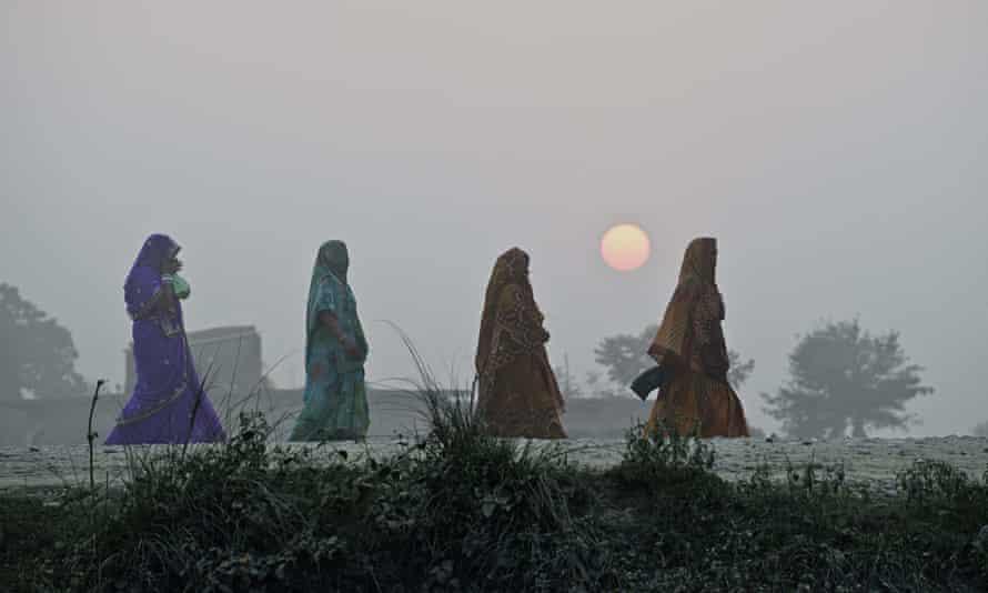 TOPSHOTS Hindu women walk on a country r