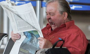 A newspaper reader yawns