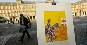 A man walks past a street painter's portrait of Don Quixote in Madrid