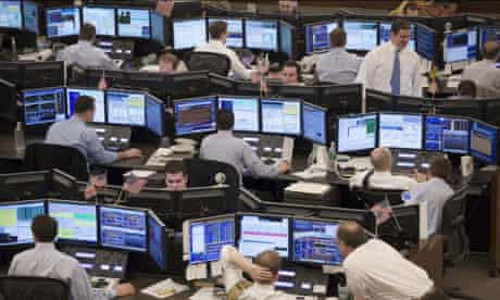 Equity traders follow stock prices on screens in Jersey City, N.J.