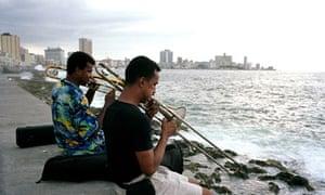 Two musicians play trombones on the sea wall in Havana, Cuba