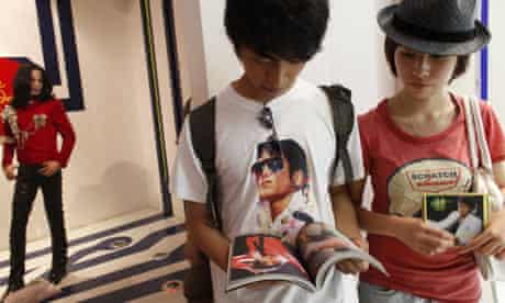 Fans browse a Michael Jackson book next to his figure at the Shanghai Madame Tussauds