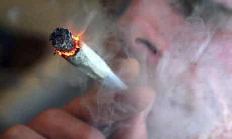 A file photo of an unidentified man smoking a cannabis cigarette at a house in London