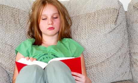 Young girl reading a book on a couch.