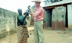 Bruce Chatwin holding a holy snake outside the Python Temple of Benin