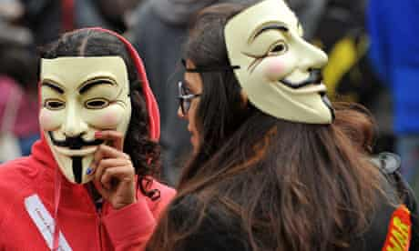 Protesters wearing Guy Fawkes masks gather outside St Paul's