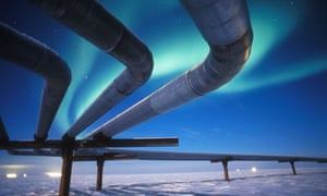 The northern lights glow above an Alaskan oil pipeline