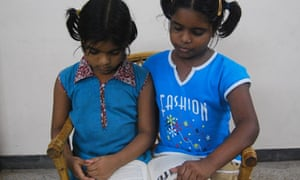 Indian sisters reading a book