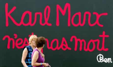 "Women walk past a giant billboard that reads "" Karl Marx is not dead""  north of Paris"