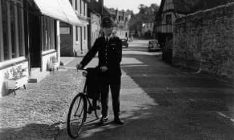 A country police constable on bicycle duty in the Surrey village of Shere