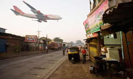 An Air India jet flies low over a Mumbai slum