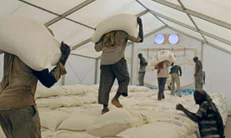 Workers carry sacks of food at a World Food Programme distribution centre in Kenya