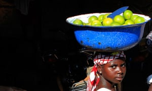 A woman carrying a bowl of fruit to market in a village near Abuja