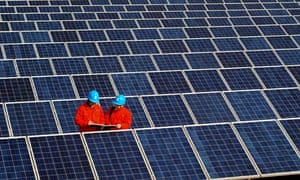 Workers check solar panels on a factory roof in Changxing, in eastern China