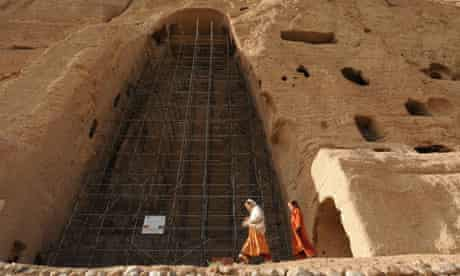 Afghan girls walk past the empty seat of one of the Buddhas in Bamiyan