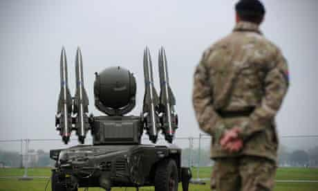 A soldier stands beside a Rapier missile defence system