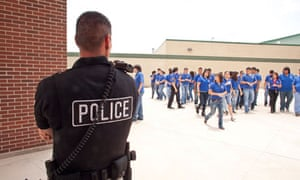 Male police officers supervise students in a high school